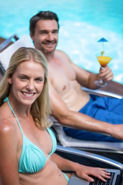 プールの近くのサンラウンジャーに座っているカップル Premium写真
