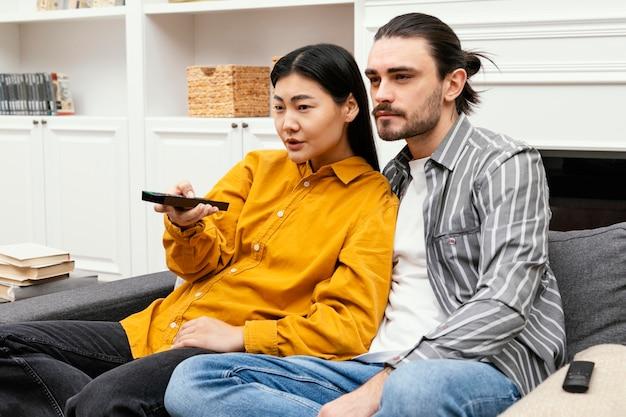 커플 소파에 앉아 Tv를 시청하고 함께 무료 사진