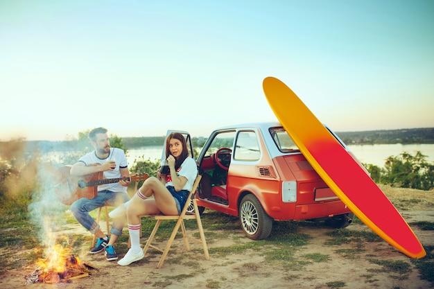Coppia seduta e appoggiata sulla spiaggia a suonare la chitarra in una giornata estiva vicino al fiume Foto Gratuite