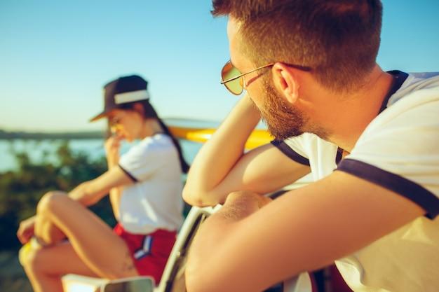 Coppie che si siedono e che riposa sulla spiaggia il giorno di estate vicino al fiume Foto Gratuite