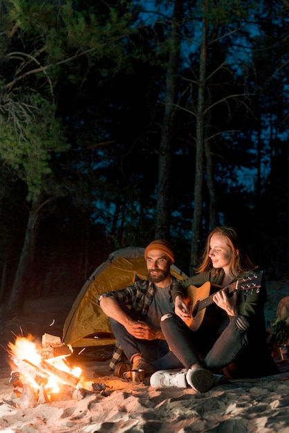 Couple sitting and singing by a tent at night Free Photo