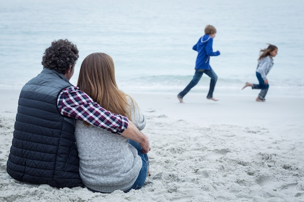 Couple sitting while children playing at sea shore Premium Photo