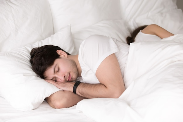 Couple sleeping peacefully together in bed, man wearing smart wr Free Photo