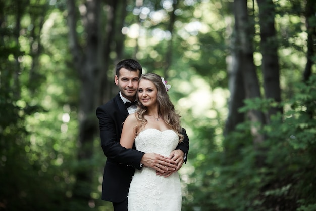 Couple of smiling newlyweds posing outdoors Free Photo