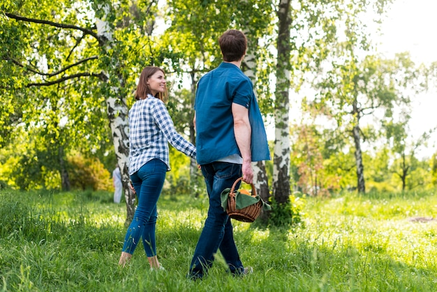 Couple smiling while going for picnic in forest Free Photo