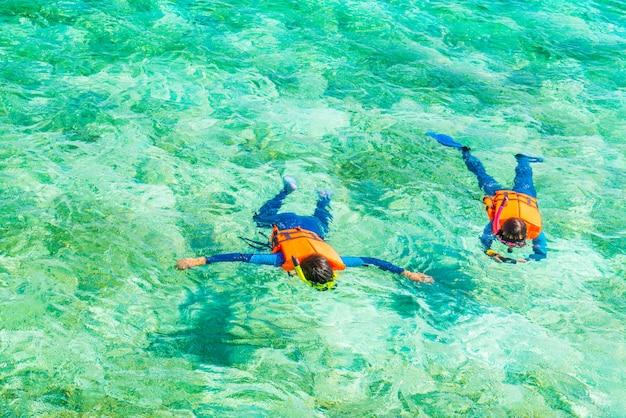 Couple snorkeling in tropical maldives island . Premium Photo