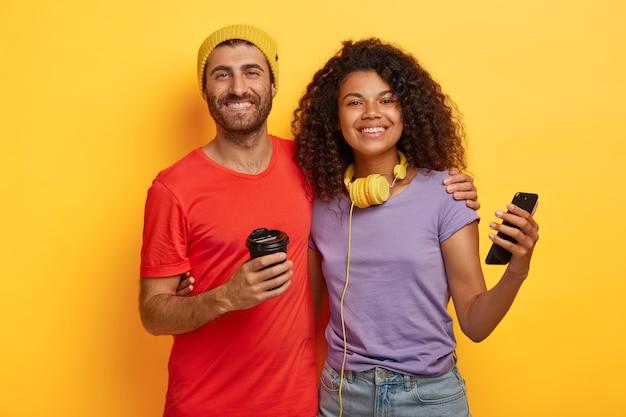 부부는 함께 자유 시간을 보내고, 커피를 마시고, 온라인 커뮤니케이션을 위해 현대적인 휴대 전화를 사용하고, 티셔츠를 입고 노란색 배경에 서로 가까이 서 있습니다. 무료 사진