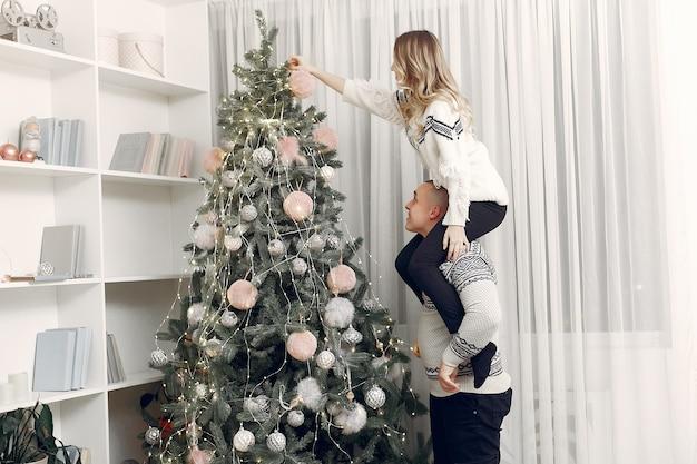 Пара проводит время дома с рождественскими украшениями Бесплатные Фотографии
