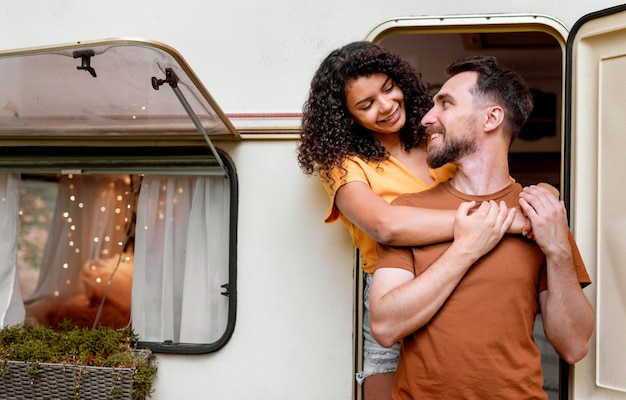 Couple standing in front of camper van and looking at each other Free Photo