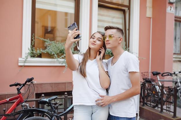 Пара, стоящая в городе с мобильным телефоном Бесплатные Фотографии