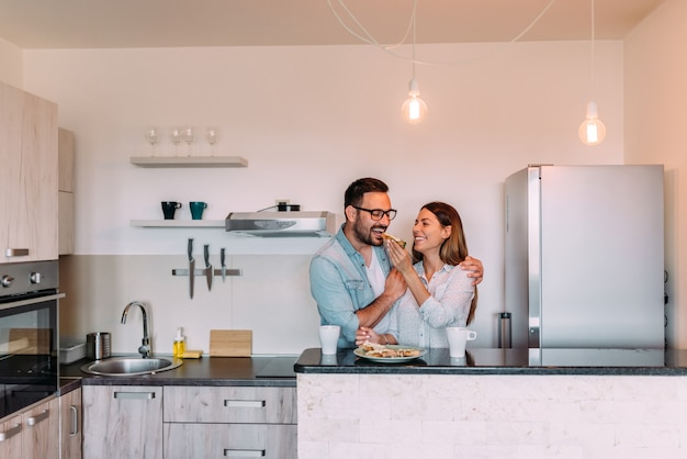 Couple standing in the kitchen of modern apartment and having breakfast together. Premium Photo