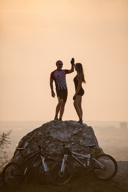 Couple standing on a rock and touches the hand to hand Premium Photo