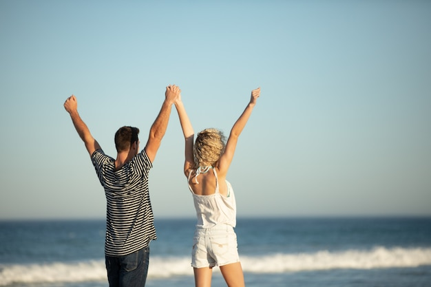 Couple standing together with arms up on the beach Free Photo