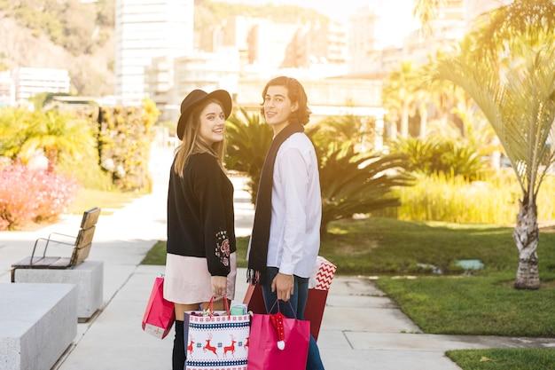 Пара, стоящая с рождественскими сумочками Бесплатные Фотографии