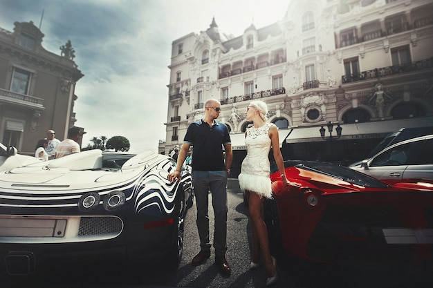 Couple stands between bugatti and lamborgini somewhere in monte carlo Free Photo