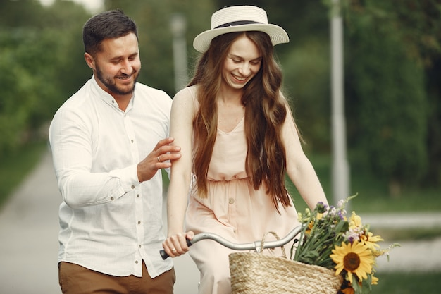 Couple in a summer park. people with vintage bicycle. girl in a hat. Free Photo