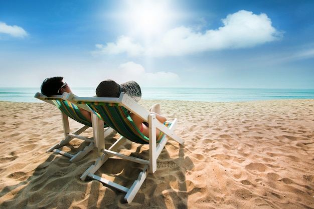 Couple sunbathing on a beach chair and umbrella Premium Photo