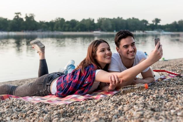 湖のそばで、selfieを取ってカップル 無料写真