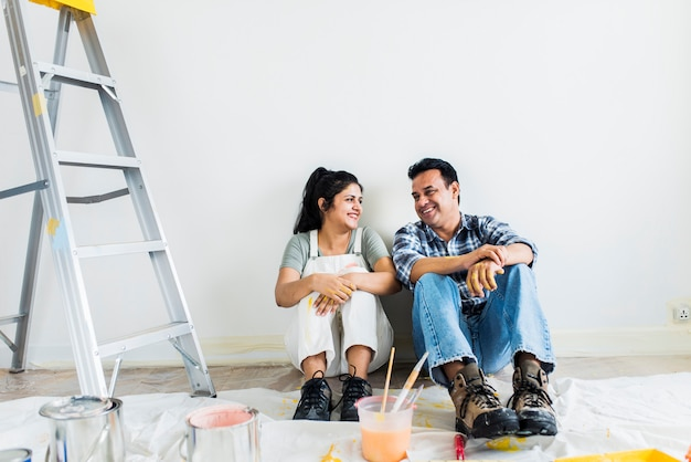 Couple taking a break from painting the walls Premium Photo