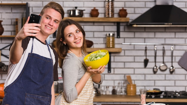 Couple taking photo with vegetable salad Free Photo