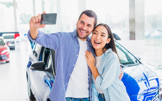 Couple taking selfie in car dealership Free Photo