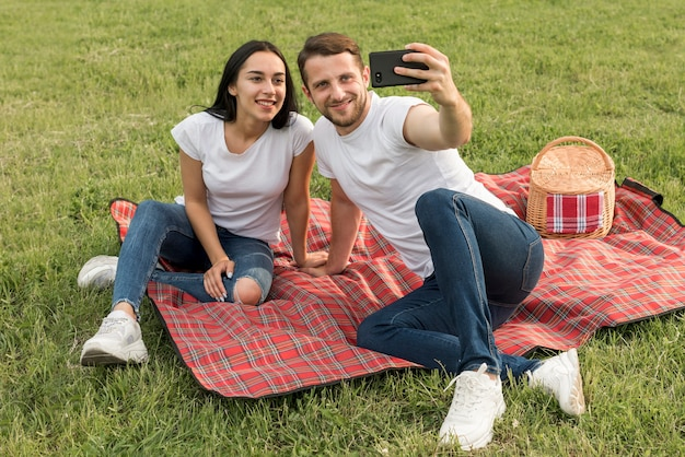 Couple taking a selfie on picnic blanket Free Photo