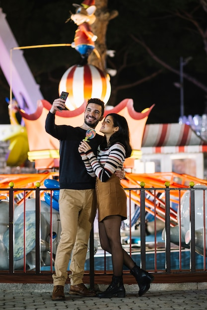 Couple taking a selfie in a theme park Free Photo