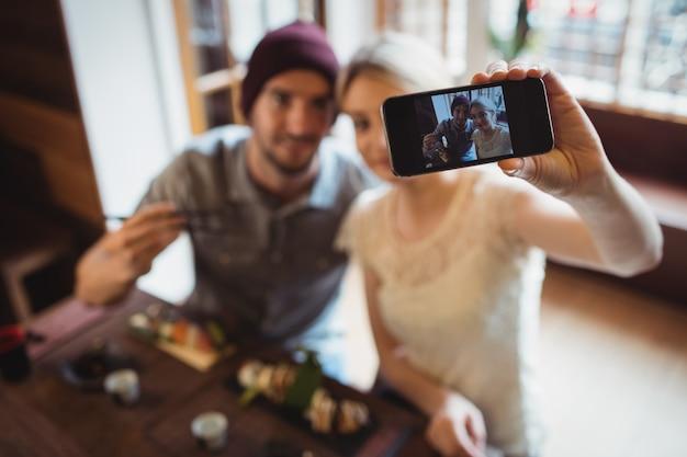 Пара, делающая селфи, имея суши Бесплатные Фотографии