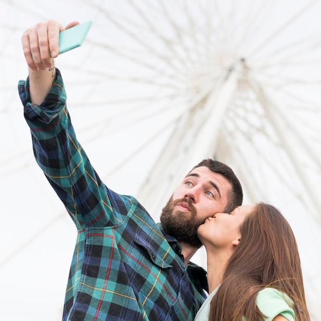 屋外でキスしながら自分撮りをしているカップル 無料写真
