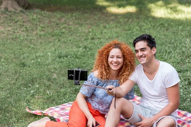 ピクニックデートにスマートフォンでselfiesを取ってカップル 無料写真