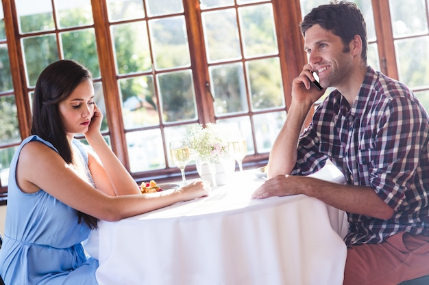 Couple talking on mobile phone in restaurant Premium Photo
