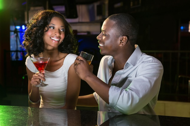Couple talking and smiling while having drinks at bar counter in bar Premium Photo