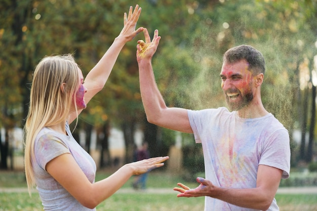 Couple throwing powder paint at each other Free Photo