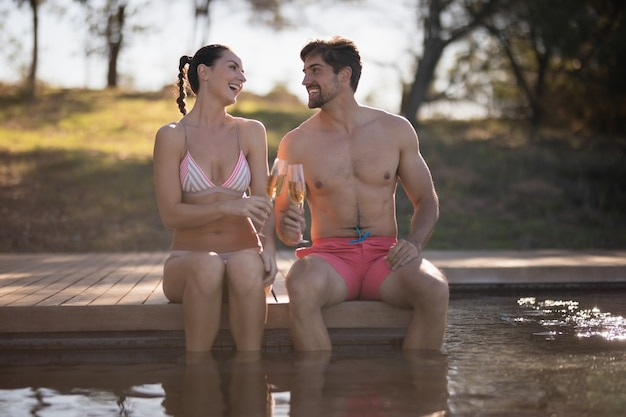 Couple toasting glasses of champagne in pool Free Photo