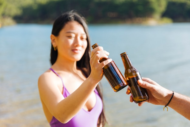 Couple toasting with bottles of beer Free Photo