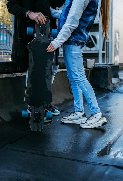 Coppia insieme all'aperto con lo skateboard Foto Gratuite