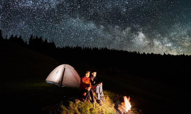 Couple tourists near campfire and tents under night sky full of stars and milky way Premium Photo