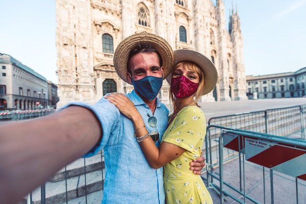 Couple of tourists wearing face mask tanking a selfie in front of the duomo of milan, italy Premium Photo