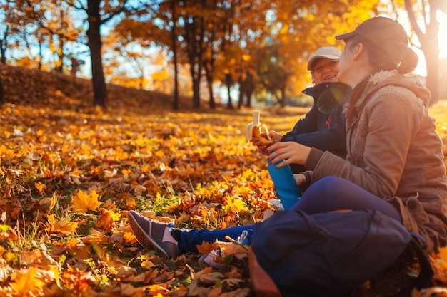 Couple of tourists with backpacks having rest in autumn forest Premium Photo