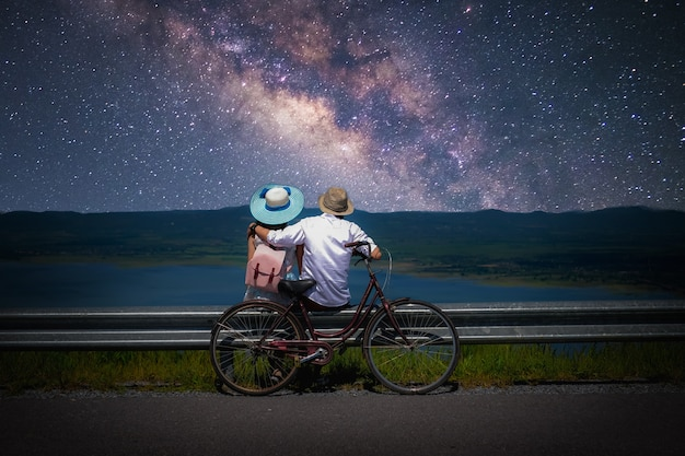 Couple traveler sitting near a bicycle and looking for the milky way and stars on the sky Premium Photo