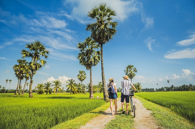 Couple traveler taking bicycle and looking for view of rice field.. Premium Photo
