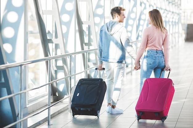 カップル旅行。愛好家の旅。空港で若い男女。家族ツアー。 Premium写真