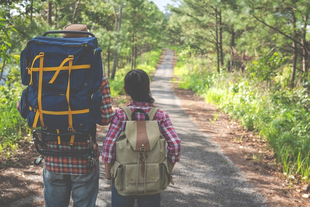 Couple on a trekking day in tropical forest along with backpacks in the forest, adventure, travel, tourism, hike. Free Photo