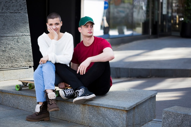 Couple in trendy clothes sitting on border near longboard Free Photo