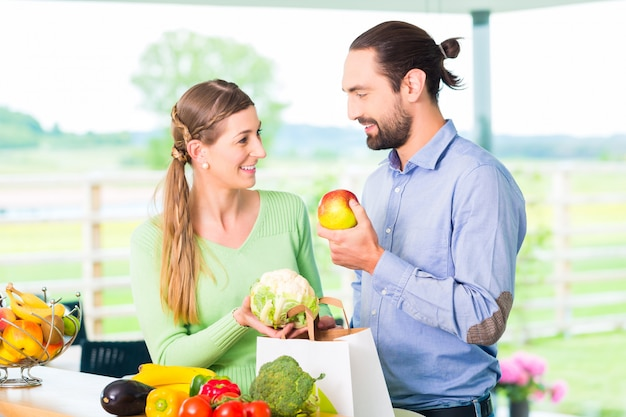 Couple unpacking grocery shopping bag at home Premium Photo