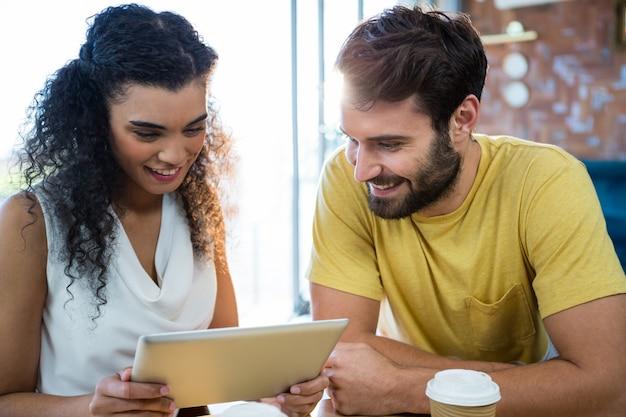 コーヒーショップでデジタルタブレットを使用してカップル Premium写真