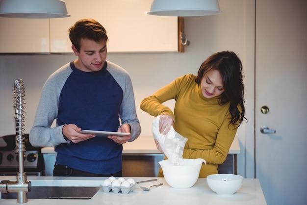 Coppia utilizzando la tavoletta digitale mentre si preparano i biscotti in cucina Foto Gratuite