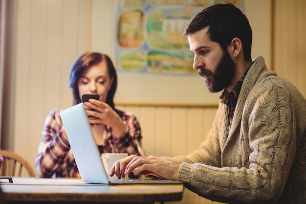 Couple using laptop and mobile phone Free Photo