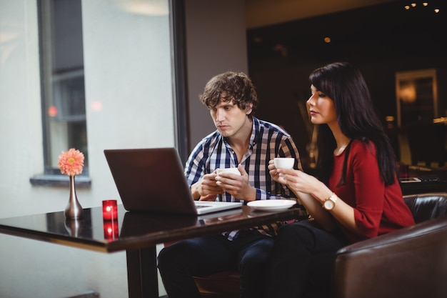 コーヒーを飲みながらラップトップを使用しているカップル 無料写真