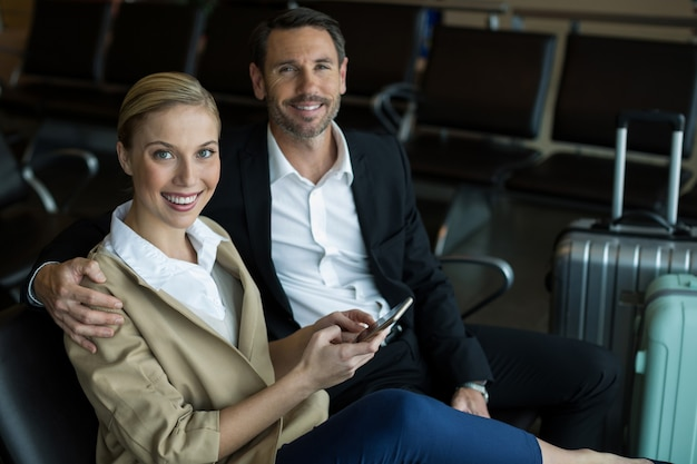 Couple using mobile phone at airport Free Photo